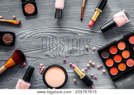 Eye shadow palette, brushes, lipstick, blusher in nude colors for make up on grey wooden background top view copyspace