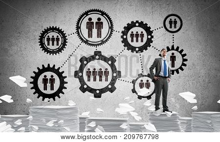 Confident businessman in suit standing on pile of documents among flying paper planes with social gear structure on background. Mixed media.