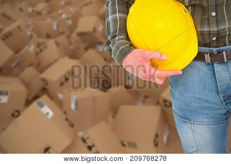 3D image of manual worker holding helmet against closed door of warehouse