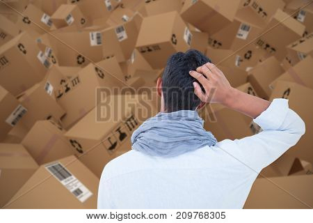 Rear view of a hipster with one hand on head against 3D image of a warehouse