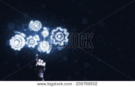 Close of businessman hand pointing with finger at gear mechanism