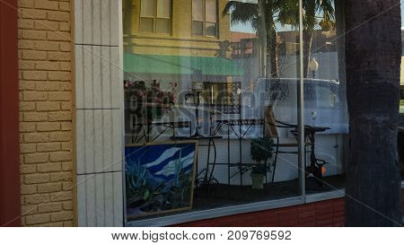Store window display, with reflection of park cars.