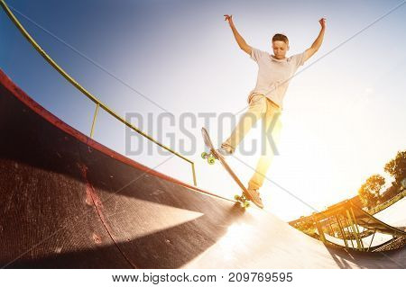 Teen skater hang up over a ramp on a skateboard in a skate park on sunset. Wide angle