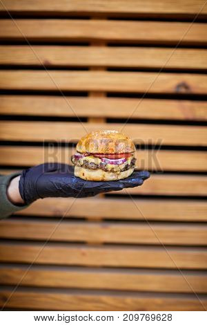 Fresh juisy burger with beef, cheese, tomato, salad, majo, onion in male hand in a black gloves on a wooden background. Close-up of burger. Food concept.