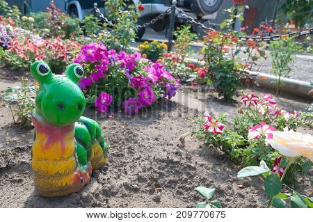 snail or helix figurine in garden designing among flowers