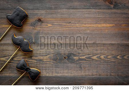 Happy father's day morning with black tie, mustache and hat cookies on sticks for celebrate on wooden background top view mock up