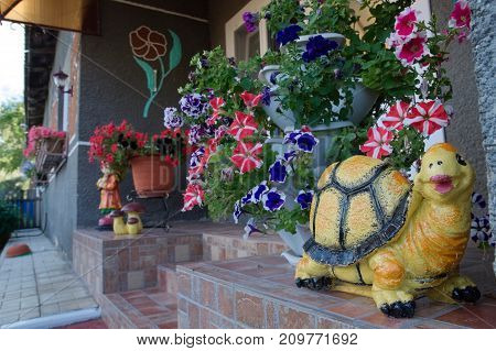 flower designing for cottage houses with flowers in pota and turtle figurines