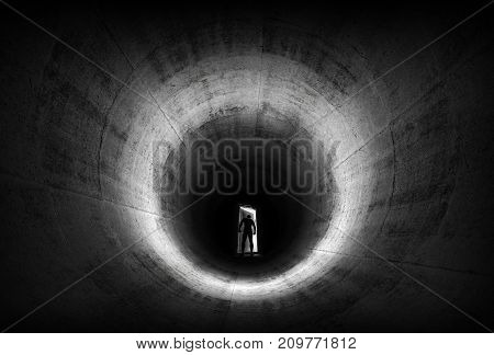 A man leaves opening door from dark concrete tunnel and looks outside to the light