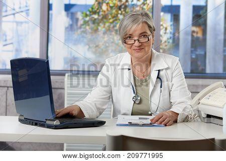 Happy female doctor working at desk in doctors room, using laptop, doing paperwork.