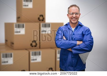 Composite 3D image of smiling warehouse manager standing with arms crossed against grey background