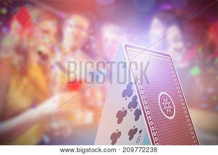 Composite 3D image of happy friends with cocktails against digital composite image of card castle