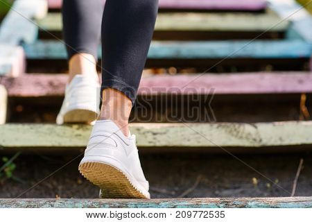 sportgirl climbs the stairs. White sneakers, black leggings and sexy legs