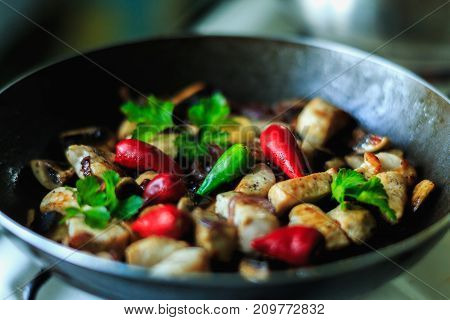 chicken pieces frying in the pan or wog with greens and red chili pepper