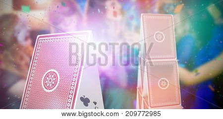 Composite 3D image of group of friends toasting glass of champagne against 3d image of card tower