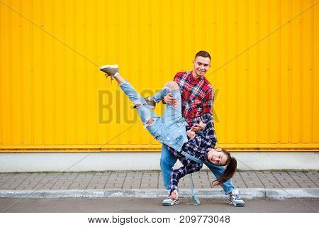 Photo of carefree young couple dancing holding hands in street and smiling, enjoying life