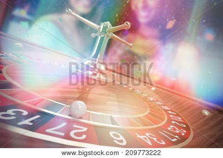 Portrait of two women having cocktail against 3d image of ball on wooden roulette wheel