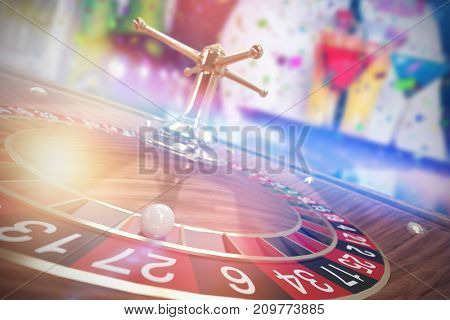 Midsection of bartender serving cocktail and martini against 3d image of ball on wooden roulette wheel