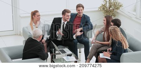 Mature manager smiling with a laptop and his business team