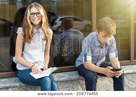 Children teenagers reading book and using smartphone.