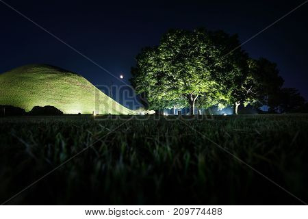 Tomb grave and trees with moon in a park at night in Gyeongju, South Korea, Asia