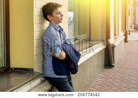 Portrait of a boy teenager 13-14 years old. Urban background