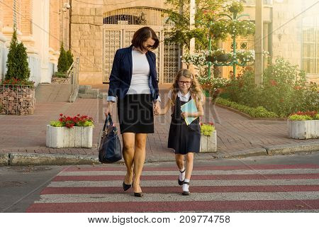 Woman and child - a young schoolgirl holding hands on zebra crossing. Education for childcare and love.