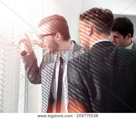 curious office staff pushes the blinds and looking out the offic
