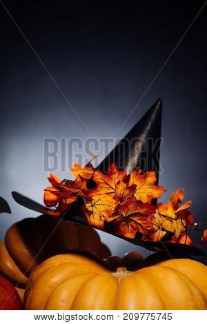 a composition for decorating a house for halloween, lie yellow and orange gourds, a large black witch hat decorated with yellow leaves
