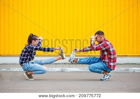portrait of carefree young couple dancing holding hands iand smiling, enjoying life on the street