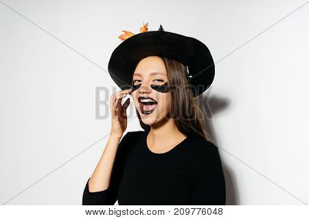 a young sexy gothic girl dressed in a witch for a halloween, in a big black hat and laughs