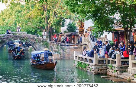 Suzhou, China - Nov 5, 2016: Boats with tourists cruised by at the historic Zhouzhuang Water Town.