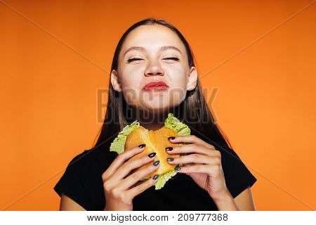 young beautiful girl wants to lose weight, but eats a large harmful high-calorie hamburger