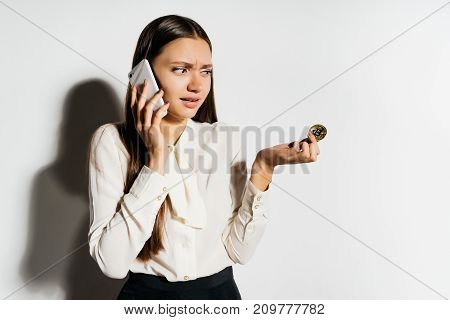 young modern successful girl talking on the phone and holding a gold beatcoin