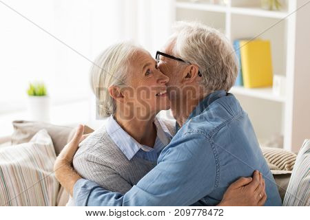 relationships, old age and people concept - happy senior couple hugging at home