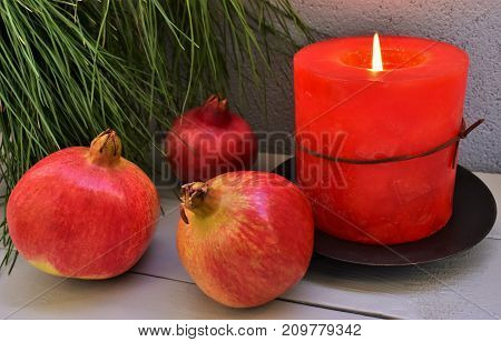 Pomegranates, candle and pine branch, Christmas still life.
