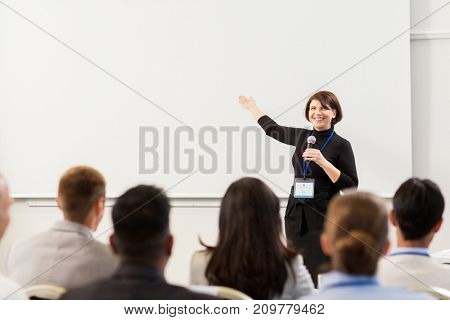 business, education and people concept - smiling businesswoman or teacher with microphone talking to group of students at conference presentation or lecture and showing something on screen