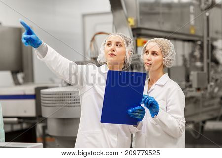 manufacture, industry and people concept - women technologists with clipboard at ice cream factory shop