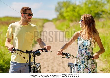people, leisure and lifestyle concept - happy young couple with bicycles on country road