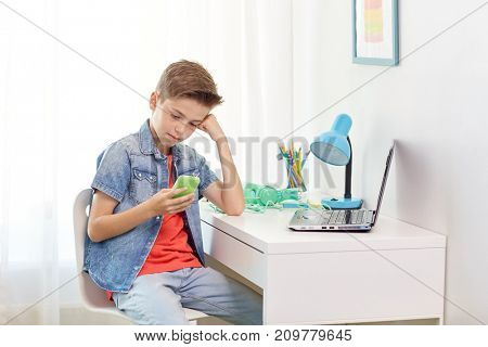 cyberbullying, people and communication concept - boy with smartphone being bullied by text message at home