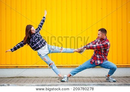 New cool portrait of carefree young couple dancing holding hands in street and smiling, enjoying life. happy together