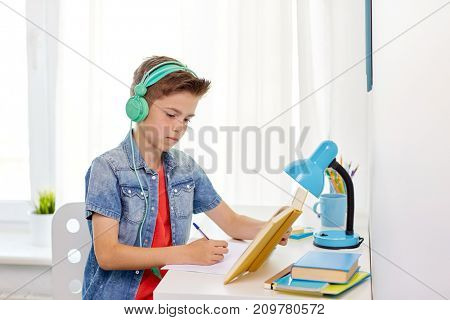 education, childhood and people concept - happy student boy in headphones writing to notebook from book at home