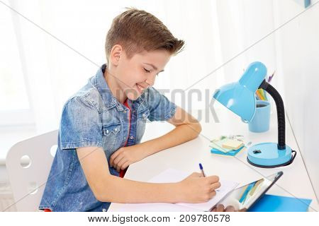 education, childhood and people concept - happy student boy with tablet pc writing to notebook at home