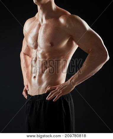 sport, bodybuilding, fitness and people concept - close up of young man or bodybuilder with bare torso over black background