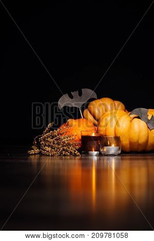 a composition for decorating a house for halloween, lie yellow and orange pumpkins, burning scented candles