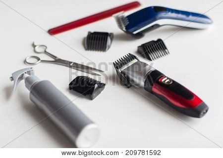 hair tools, hairstyle and hairdressing concept - styling sprays, trimmers or clippers with scissors and attachment combs on white background