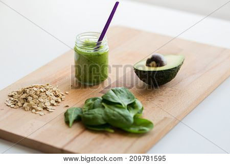 baby food, healthy eating and nutrition concept - glass jar with green vegetarian puree on wooden cutting board