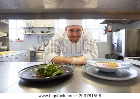food cooking, profession and people concept - happy male chef cook with plate of soup and salad at restaurant kitchen table