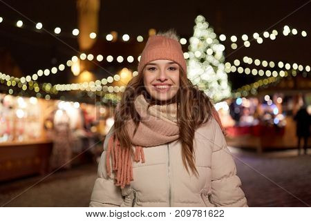 holidays and people concept - beautiful happy young woman at christmas market in winter evening