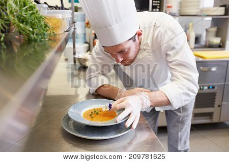 food cooking, profession and people concept - happy male chef cook serving and decorating plate of soup with flower at restaurant kitchen
