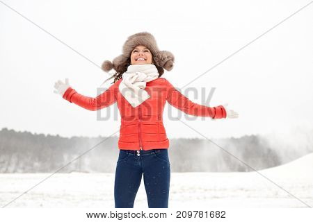 people, season and leisure concept - happy woman in winter fur hat having fun outdoors